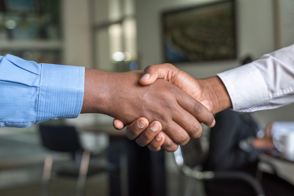 Duas pessoas de roupa social dando um aperto de mãos